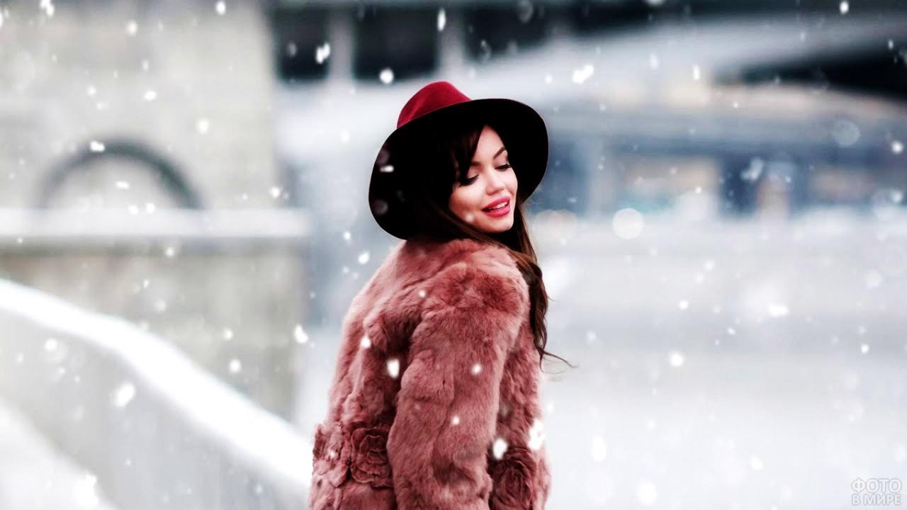 Брюнетка в шубе и шляпе под снегопадом