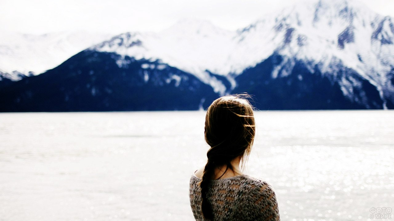 Девушка с косой смотрит на горное озеро