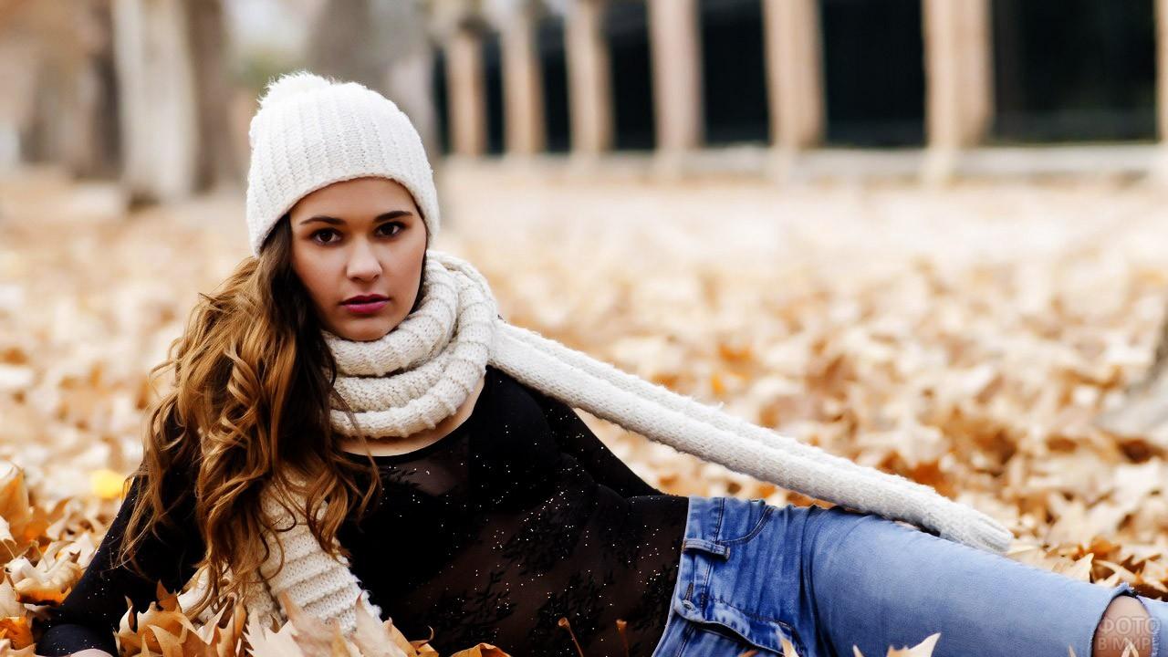 Девушка в белых шапке и шарфе лежит на первом снегу в парке
