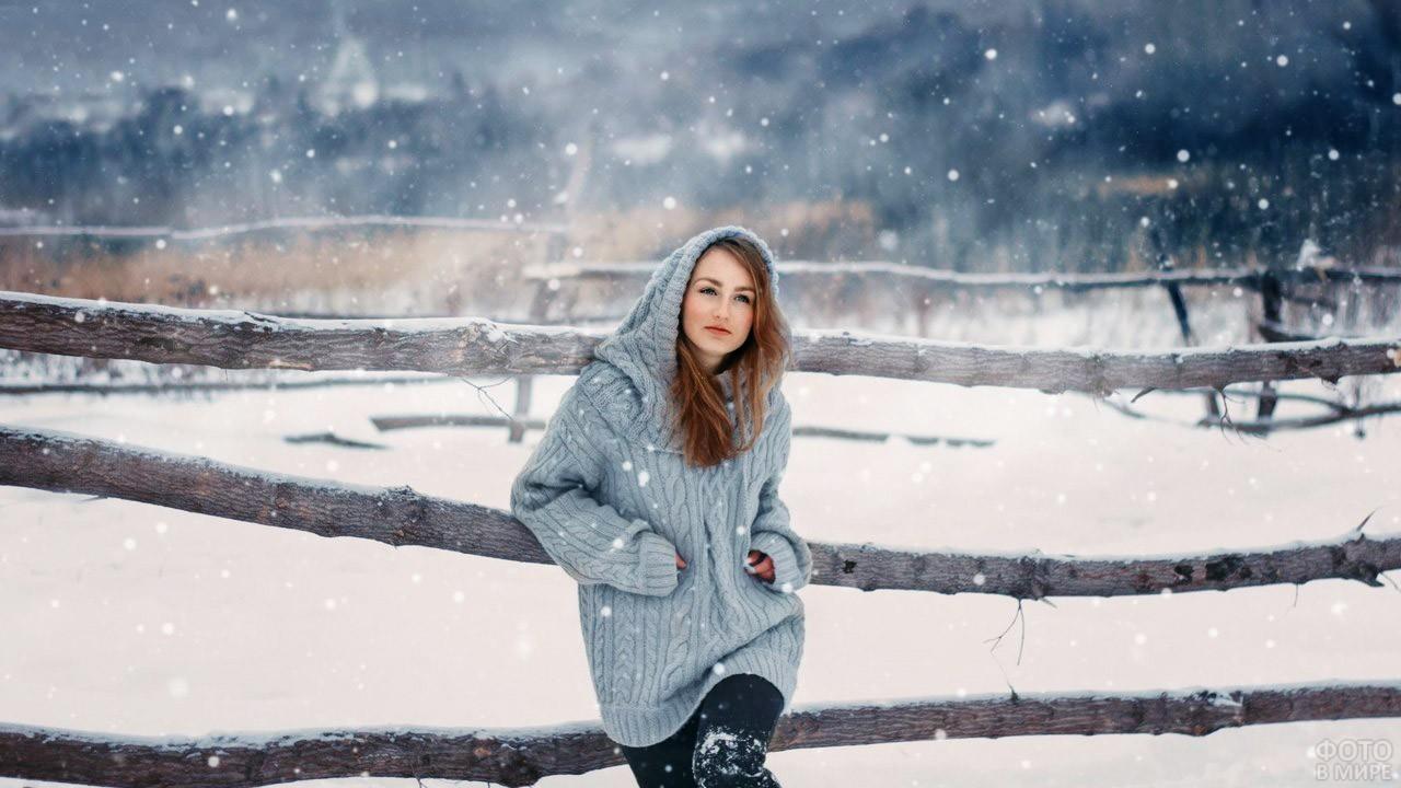 Юная шатенка в вязанной кофте с капюшоном на зимней ферме