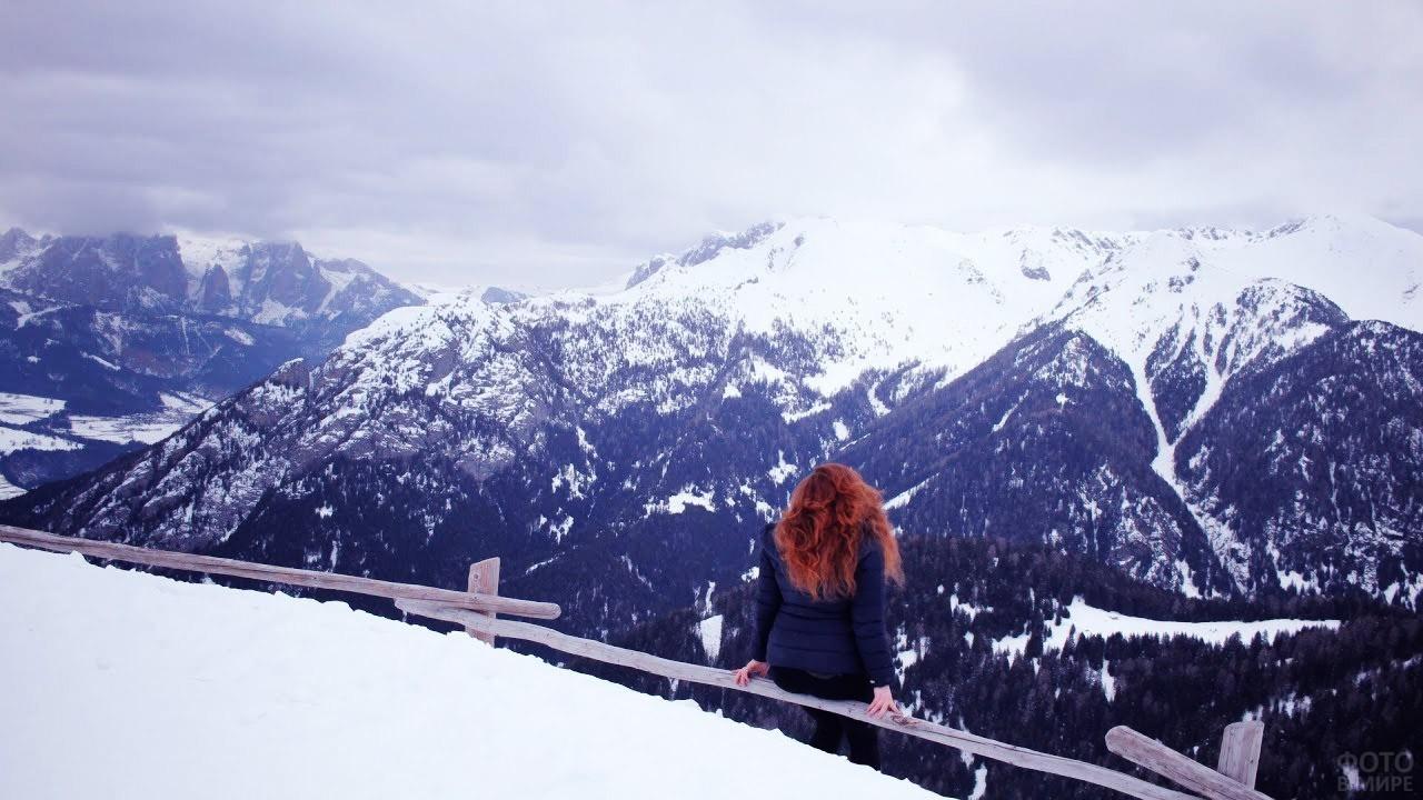 Рыжеволосая девушка на смотровой площадке с видом на горы