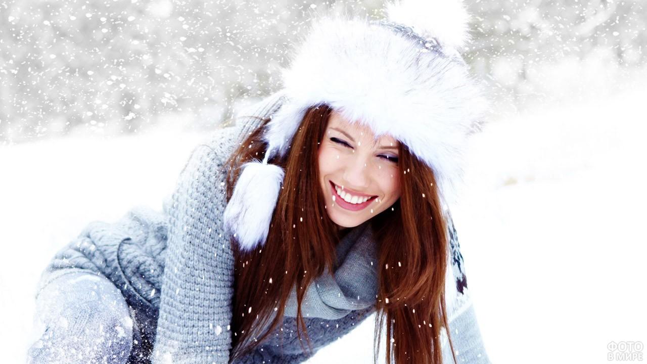 Счастливая девушка дурачится в снегу