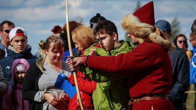 Волонтёр-реконструктор показывает подростку, как стрелять из лука