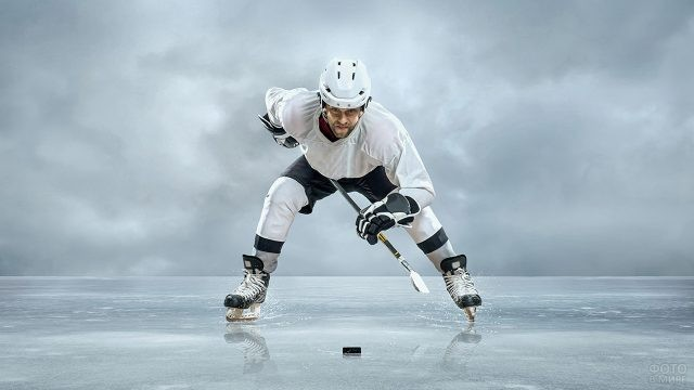 Хоккеист пристально смотрит на шайбу на льду