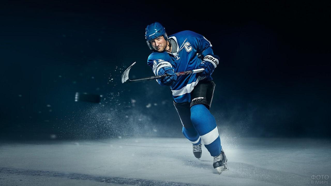 Хоккеист в синей форме посылает шайбу