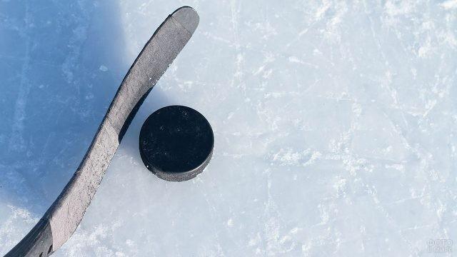 Хоккейная клюшка и шайба на льду