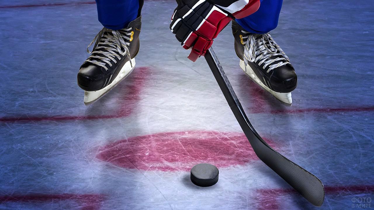 Клюшка и шайба у ног хоккеиста
