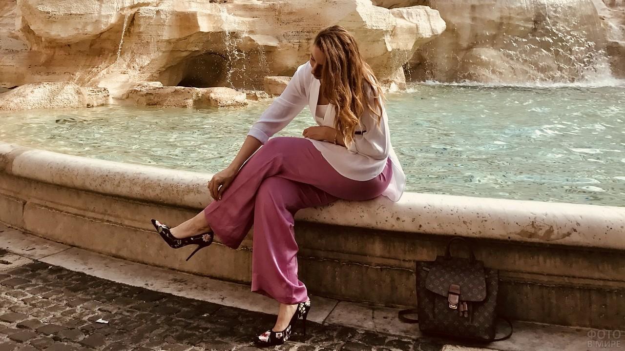 Девушка присела на бордюр фонтана