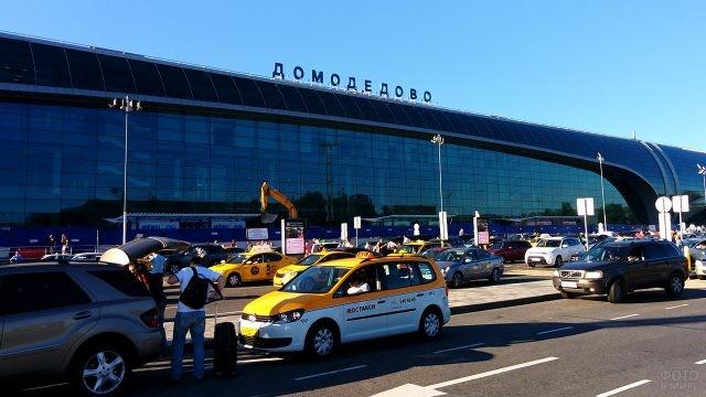Такси и автомобили на парковке у входа