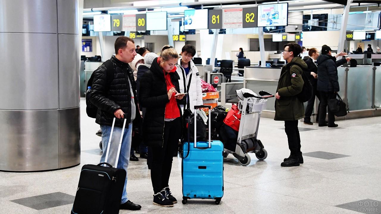 Туристы в зале регистрации пассажиров