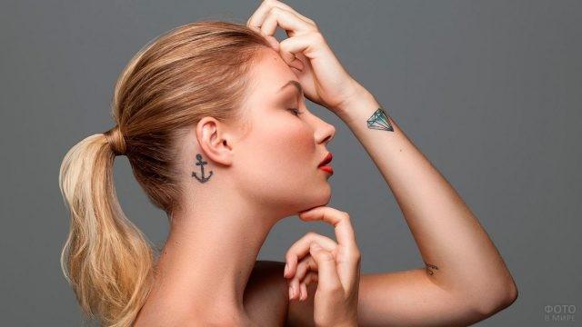Блондинка с татуировками на руке и шее