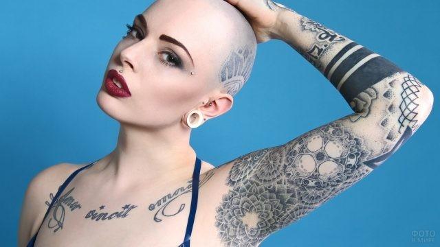 Лысая девушка с татуировкой в виде надписи на декольте