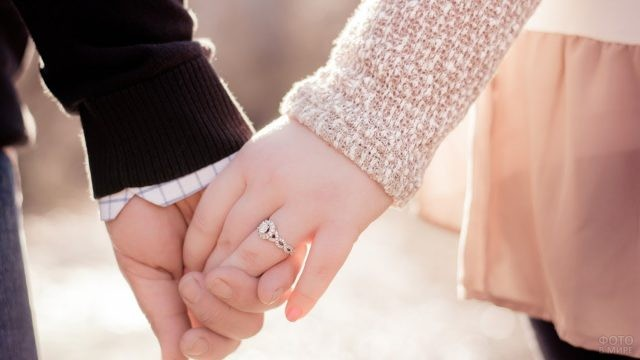 Парень держит пальцы девушки