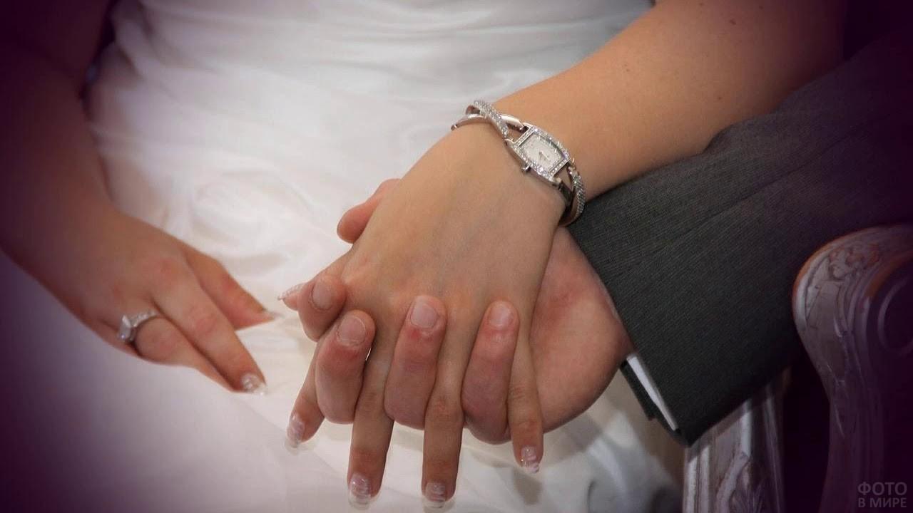 Парень держит руку девушки с часиками