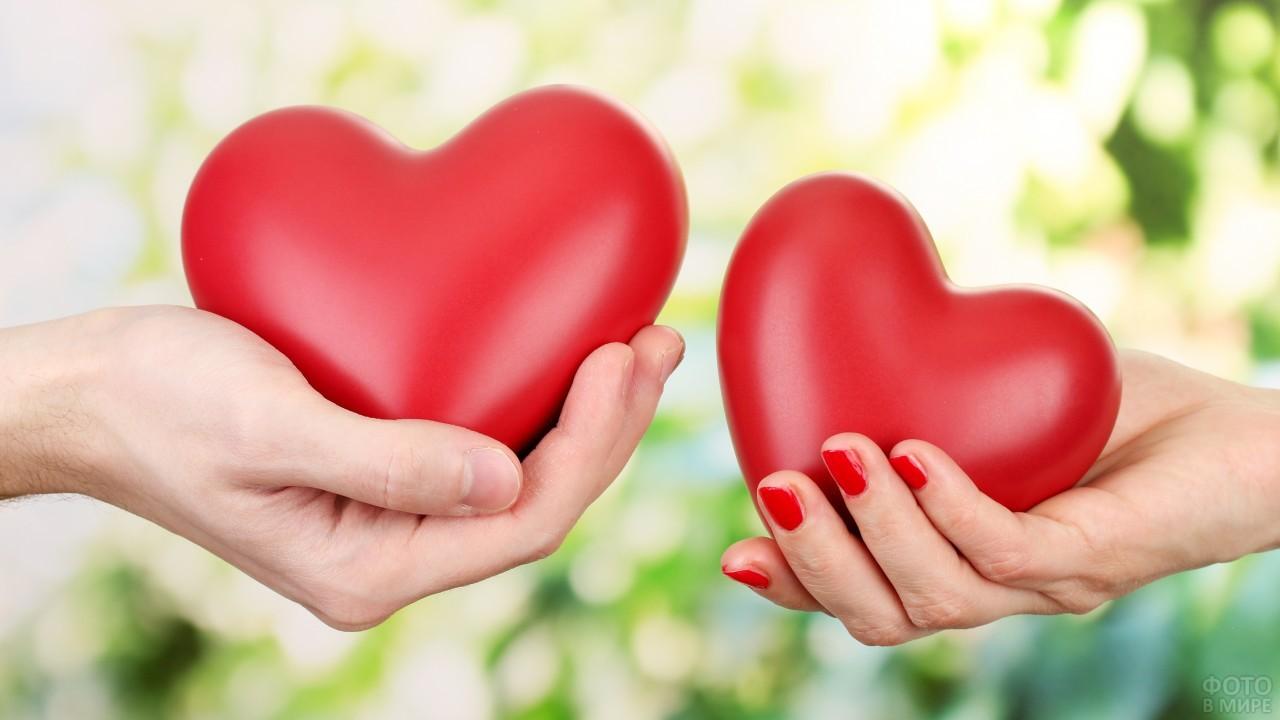 Парень и девушка держат красные сердечки
