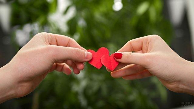 Парень и девушка держат сердечки