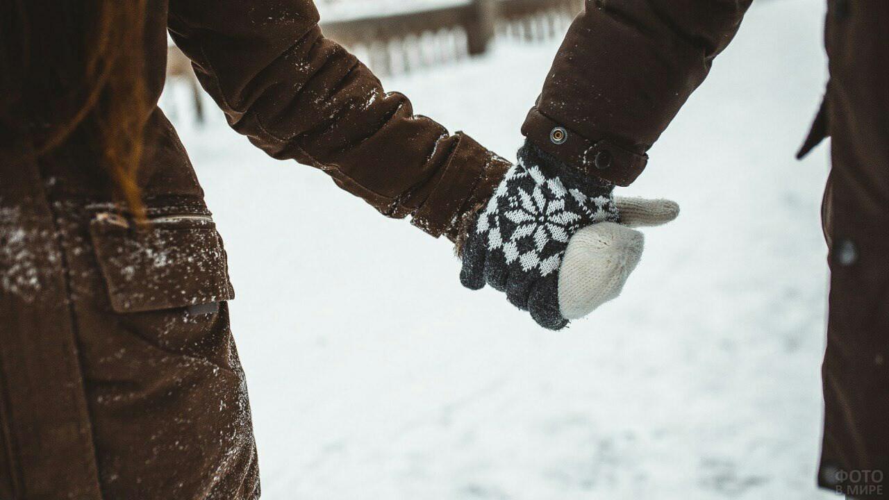 Парень и девушка в варежках держатся за руки