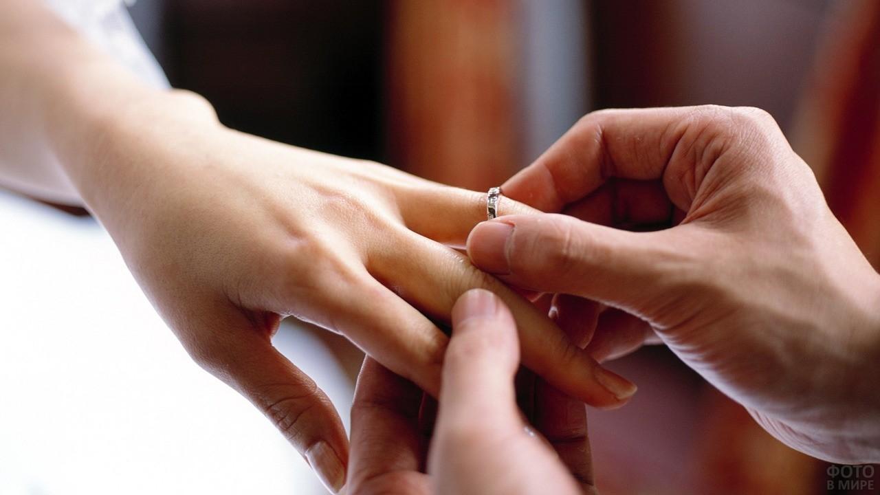 Парень надевает кольцо на руку девушки