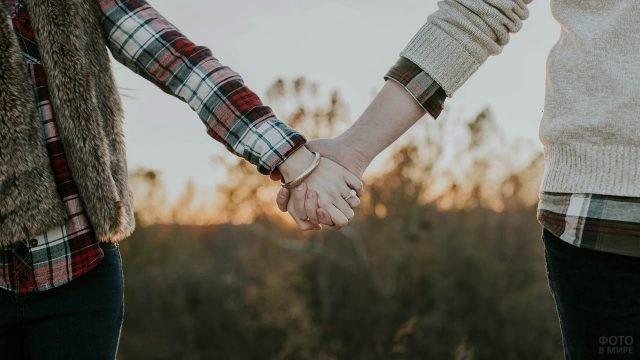 Рука девушки с колечком держит руку парня