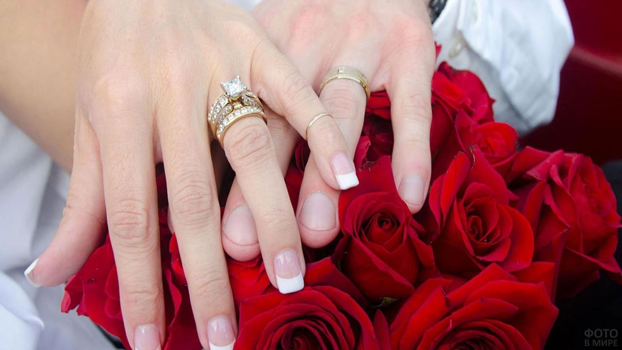 Руки лежат на красных розах
