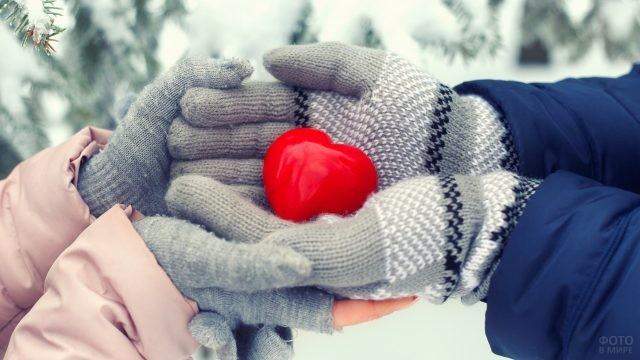 Руки парня и девушки в перчатках держат сердечко