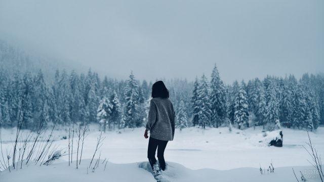 Брюнетка в свитере идёт по снегу