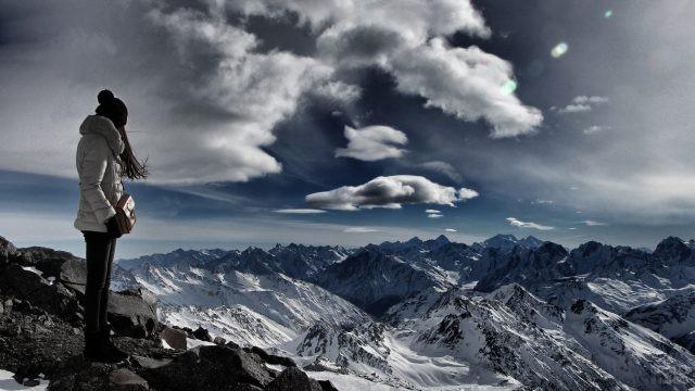 Девушка с сумкой стоит на вершине горы