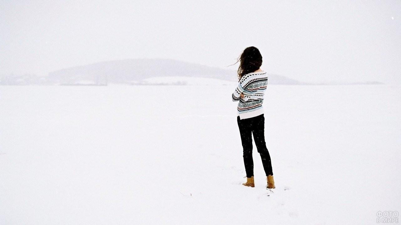 Девушка в кофте стоит на снегу