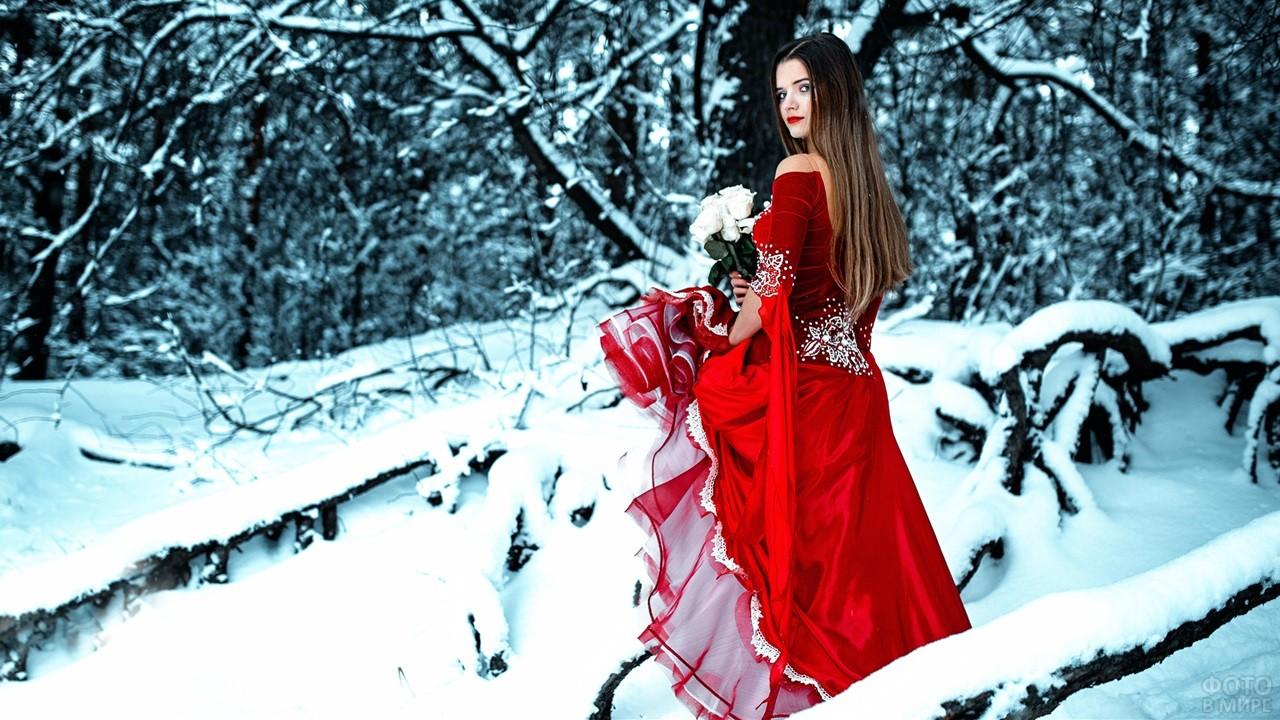 Девушка в красном платье держит белые розы