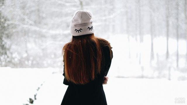 Девушка в пальто и шапочке стоит в лесу
