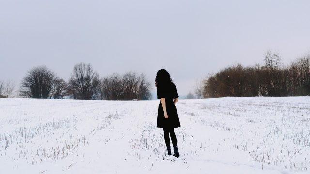 Девушка в платье идёт по снегу