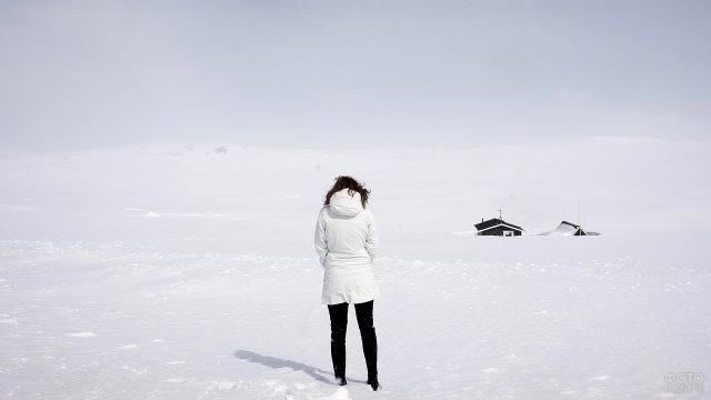 Девушка в снежном поле смотрит на домики