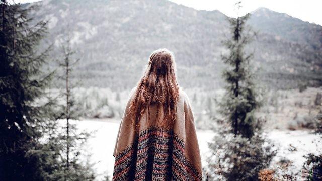 Длинноволосая девушка смотрит на горы
