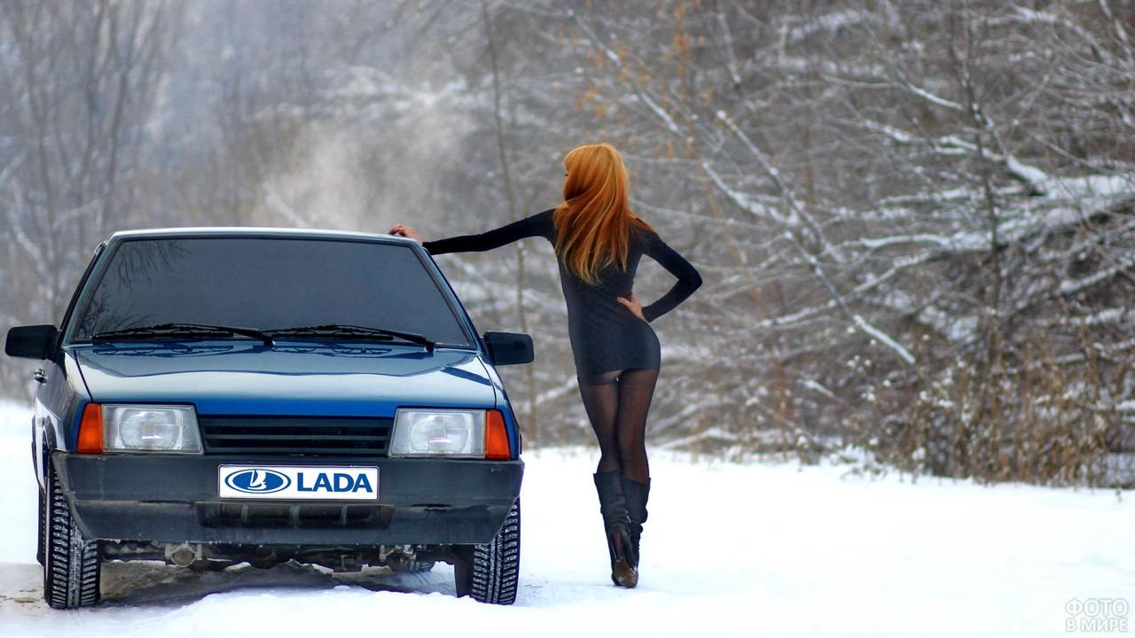 Рыжеволосая девушка стоит у машины