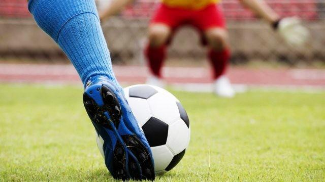 Нога в бутсе пинает мяч