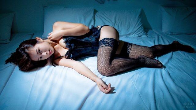 Азиатская девушка лежит на кровати