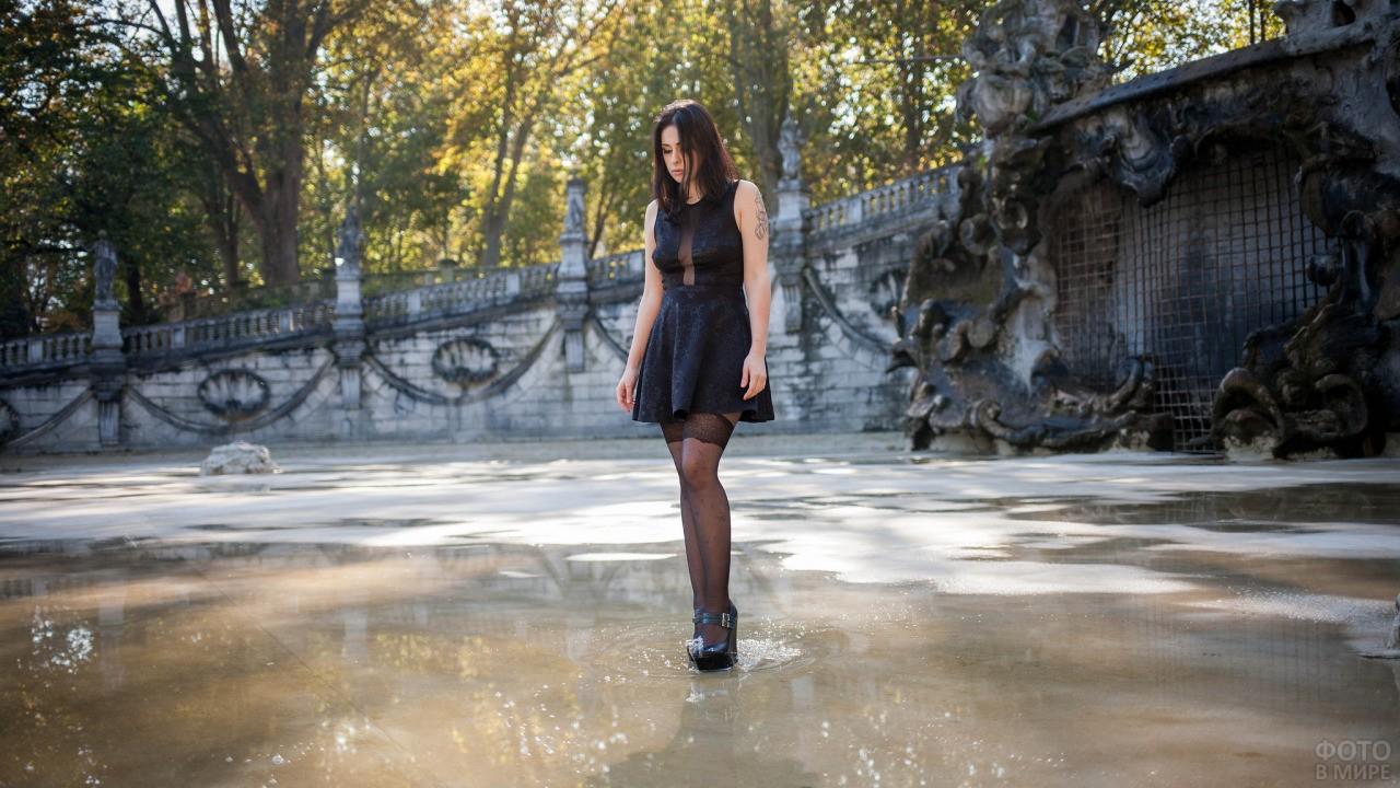 Девушка на каблуках стоит в луже