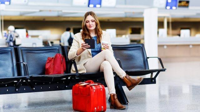 Девушка с багажом в зале ожидания