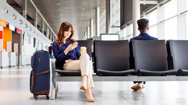 Девушка с кофе и мобильным в зале ожидания