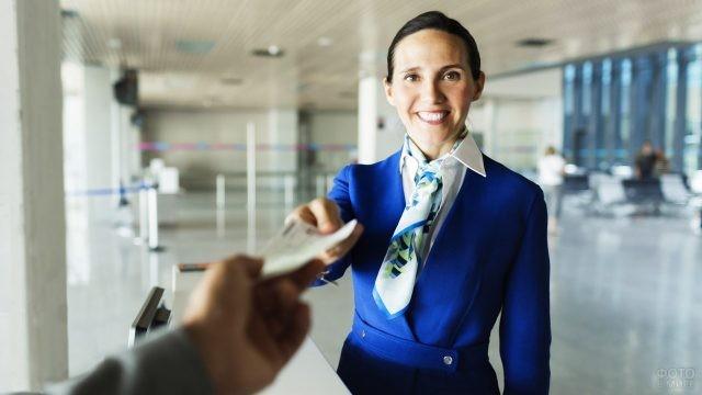 Работница аэропорта протягивает проверенный билет пассажиру