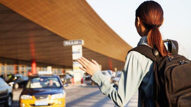 Туристка ловит такси у пассажирского терминала