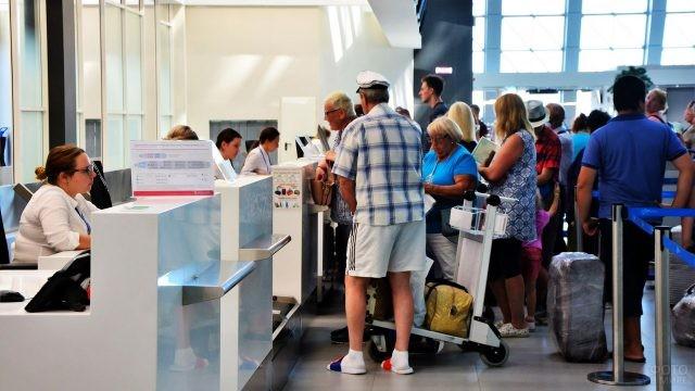 Туристы у стойки регистрации в аэропорту Симферополя