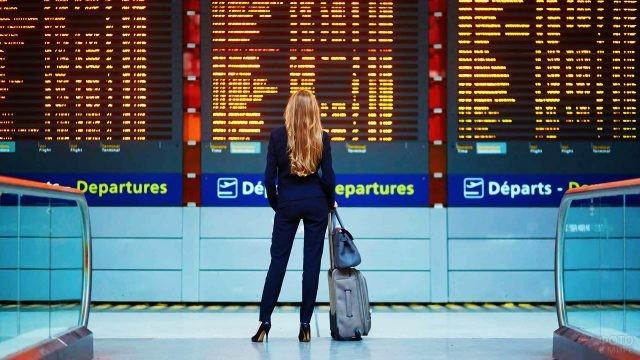 Женщина с багажом смотрит на табло вылетов