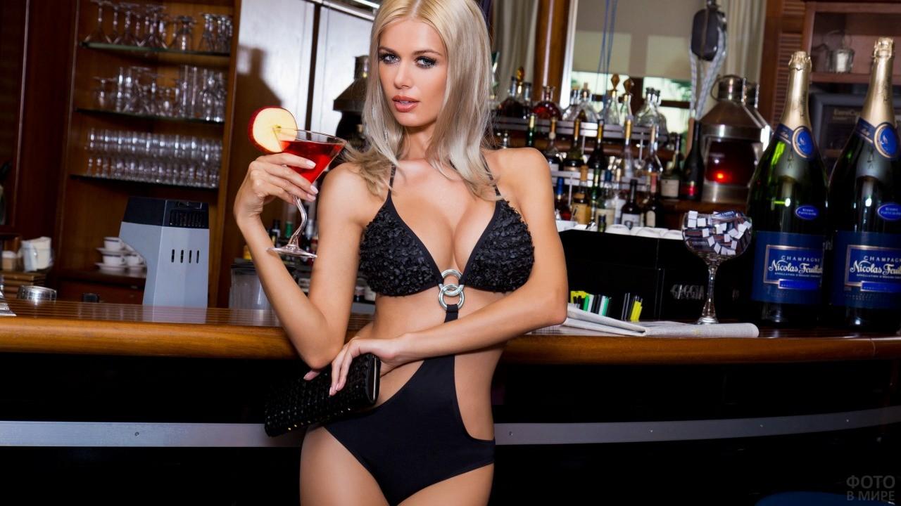 Блондинка у барной стойки с фужером в руке