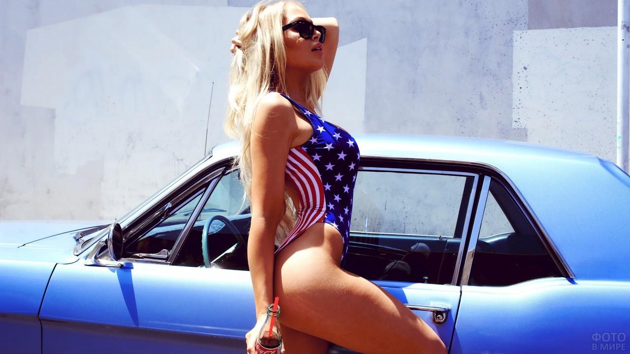 Блондинка в купальнике стоит у машины