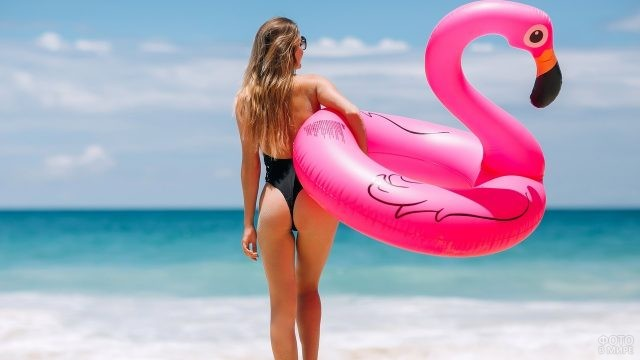 Девушка идёт к морю с надувной игрушкой