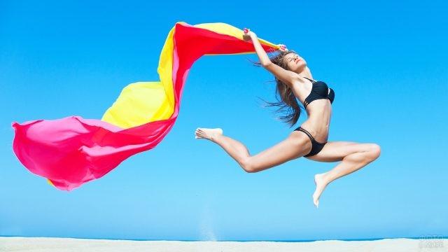Девушка прыгает с яркой тканью