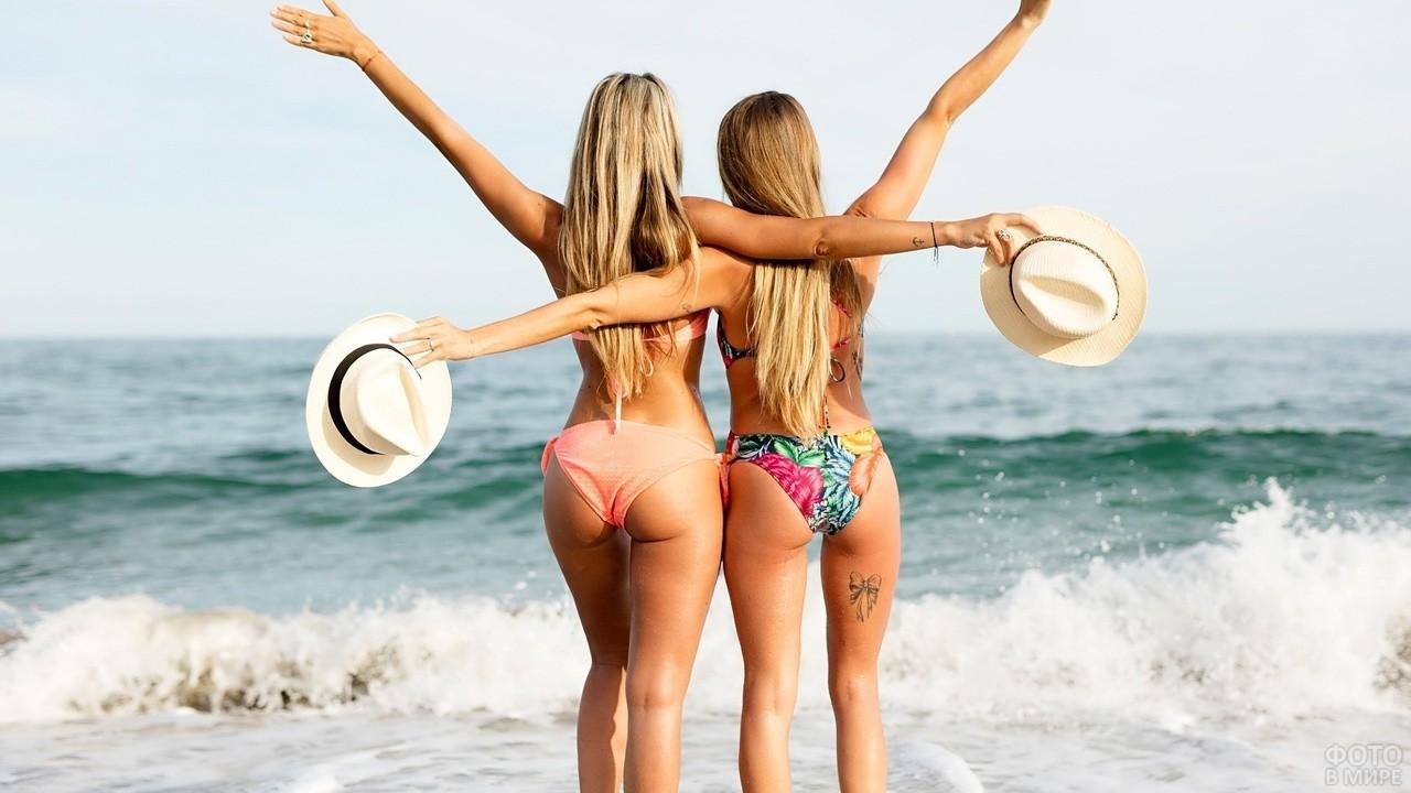 Две блондинки с распахнутыми руками смотрят на море