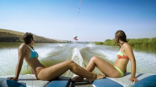 Две девушки на катере, буксирующем сёрфингиста