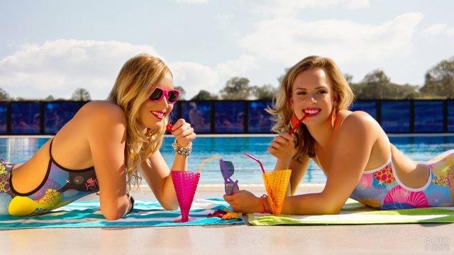 Две девушки отдыхают у бассейна